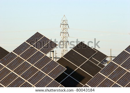 An array of solar panels with an electric tower in the background - stock photo