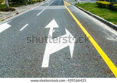 An arrow on the road - stock photo