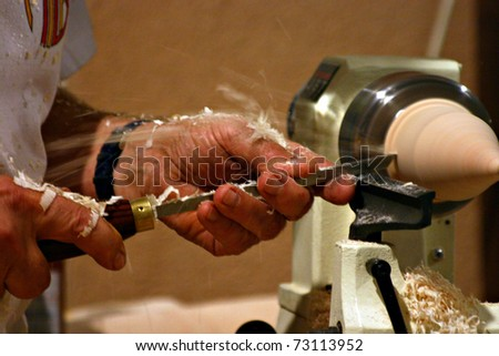 An artisan is carving wood accurately. The hands are full of wood shavings