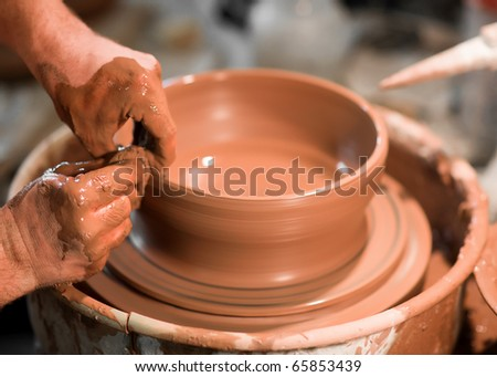 An artist makes clay pottery on a spin wheel. - stock photo