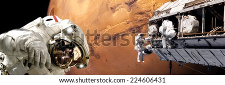 An artist's depiction of  a team of astronauts performing work on a space station while orbiting above the surface of Mars. Elements of this image furnished by NASA. - stock photo