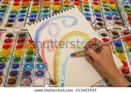 An artist's hand paints pastel colored swirls on watercolor paper using colorful paints against a background of watercolor paint pans - stock photo