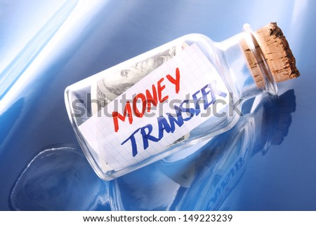 """An artistic banking concept. A banknote and a message in a bottle saying """"Money transfer""""  - stock photo"""
