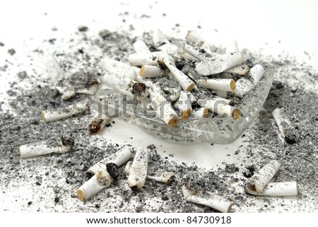 An ashtray is overflowing with burnt cigarette butts. - stock photo
