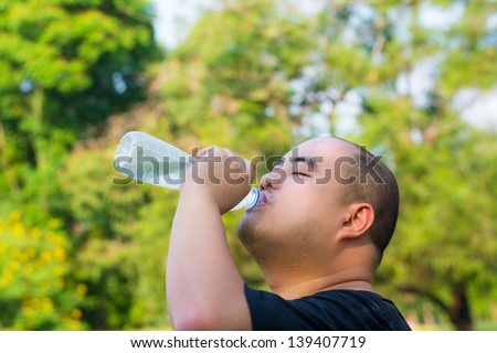 An Asian bald head guy is drinking water with thirst