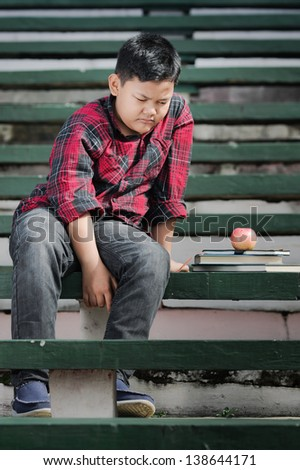 an asian boy sitting on a green concrete bench with sad expression - stock photo