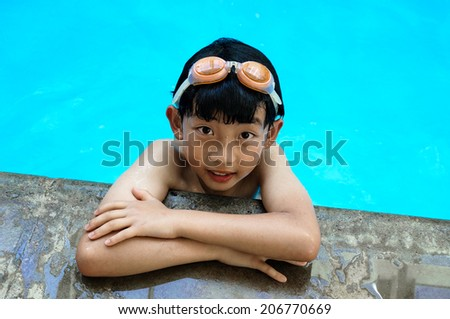 An Asian boy takes a poolside break at a swimming pool. - stock photo