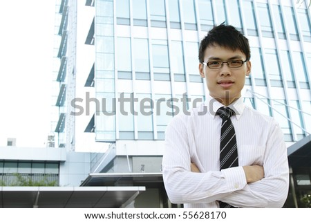 An Asian business executive standing in front of an office building - stock photo