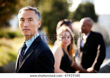 An Asian business man with a serious expression and colleagues in the background