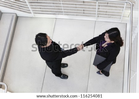 An asian business team shaking hands from above