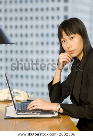 An Asian business woman sitting at a desk in hotel room with laptop computer (shallow depth of field used)