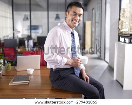 an asian businessman holding cup of coffee sitting on desk in office, smiling and cheerful. - stock photo