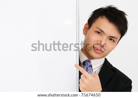 An Asian businessman pointing at a blank whiteboard - stock photo