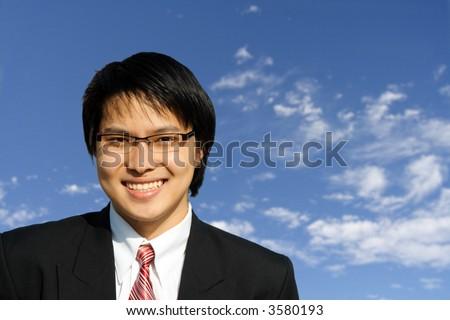 An asian businessman posing outdoor against blue sky - stock photo