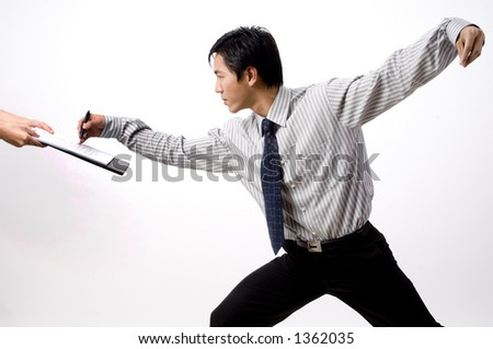 An asian businessman signs a contract whilst practising Tai Chi