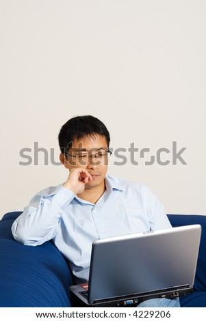 An asian businessman working on his laptop at home - stock photo