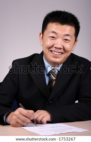 An asian businessman writting a document. - stock photo
