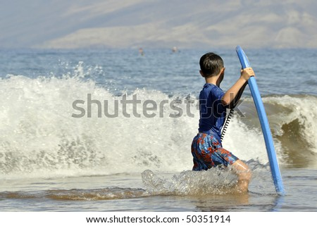 An Asian Child carrying a boogie board - stock photo