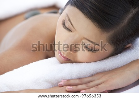An Asian Chinese woman relaxing at a health spa while having a hot stone treatment or massage - stock photo