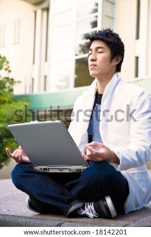 An asian college student doing meditation while holding a laptop