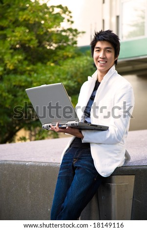 An asian college student holding a laptop at the campus - stock photo