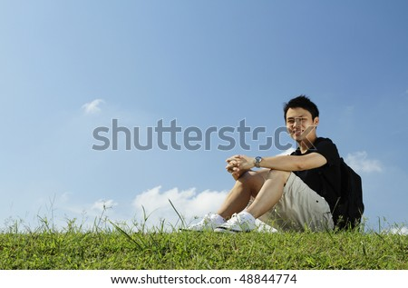An Asian college student sitting on grass - stock photo