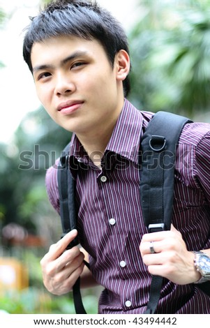An Asian college student smiling carrying a bag outdoors - stock photo