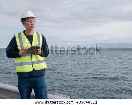 An asian engineer holding a tablet and standing in front of semi submersible oil rig - stock photo