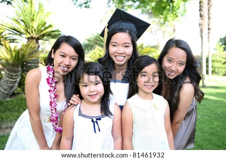 An asian family of girls and sisters celebrating a college graduation - stock photo