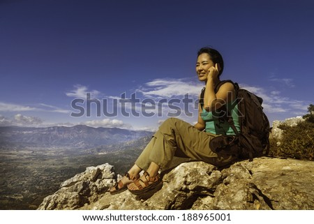 An Asian female hiker talks on a cell phone while sitting on a mountain top in Sardinia, Italy. - stock photo