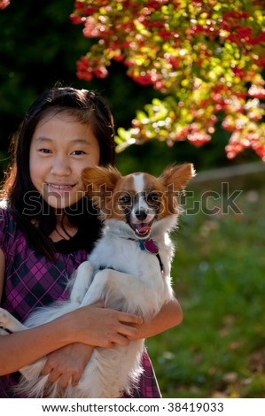 An Asian girl is playing with her dog at Luther Burbank park