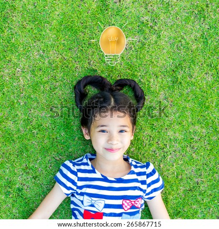 An asian  kid with heart-shaped hair on grass with a golden egg in light bulb shape over the girl's head: Kid's idea and imagination - stock photo