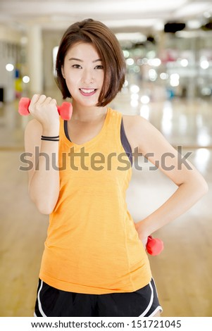 An Asian lady doing weight lifting exercise in a gym. - stock photo