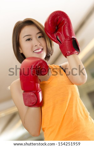 An Asian lady in boxing pose in a gym. - stock photo