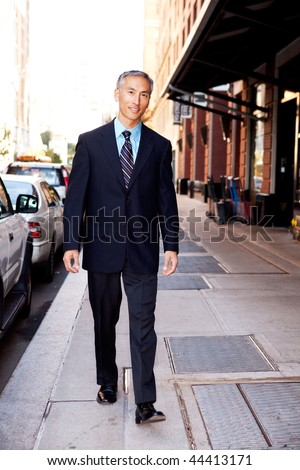 An asian looking business man walking in a street - stock photo