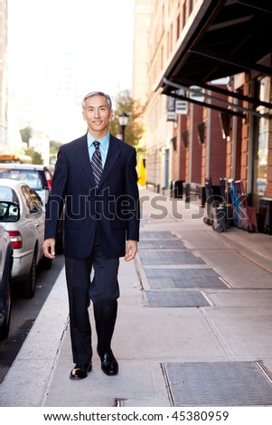 An asian looking business man walking in a street