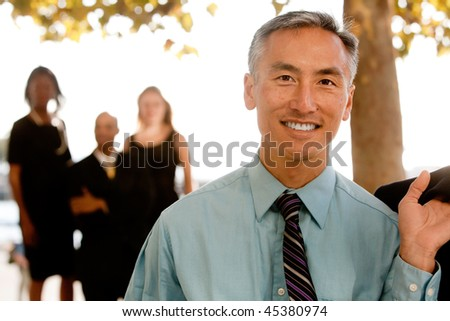 An asian looking business man with colleagues in the background - stock photo