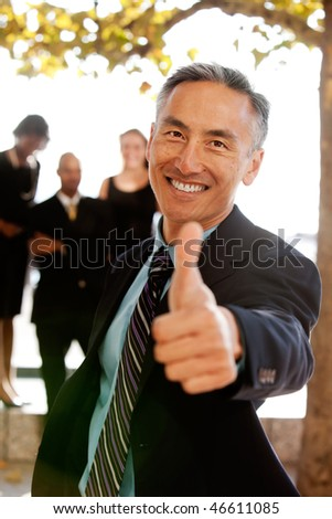 An asian looking business man with thumbs up - critical focus on eyes - stock photo