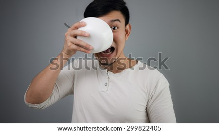 An Asian man eating with white bowl.