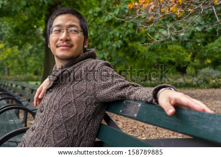 an asian man in his twenties relaxing on a bench in a park - stock photo