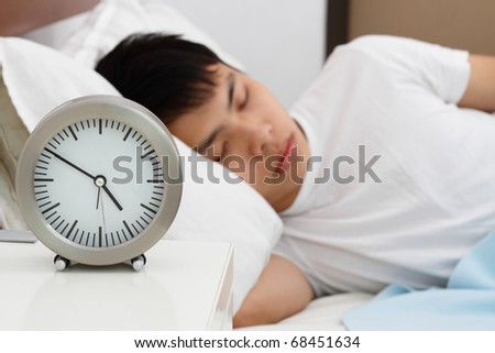 An Asian man sleeping with a clock in the foreground. Focus is on the clock.