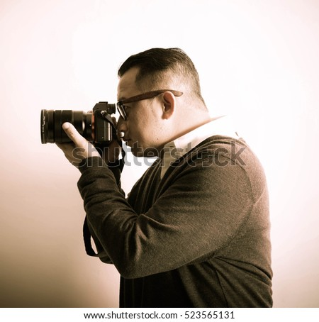An asian man with camera in actions.