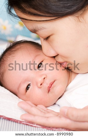 An asian mother kissing her baby boy - stock photo