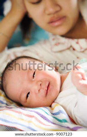 An asian mother watching her cute smiling baby boy - stock photo