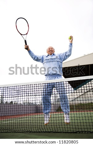 An asian senior tennis player jumping for joy - stock photo