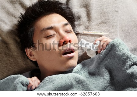An Asian sick man, sleeping with thermometer showing high temperature - stock photo