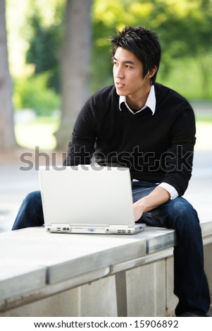 An asian student working on his laptop at the campus