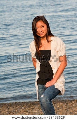 An Asian teenage girl standing by the beach - stock photo