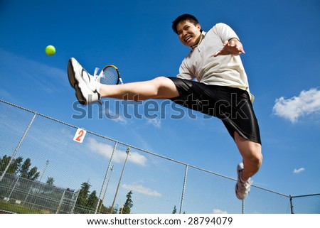 An asian tennis player jumping in the air hitting a tennis ball - stock photo