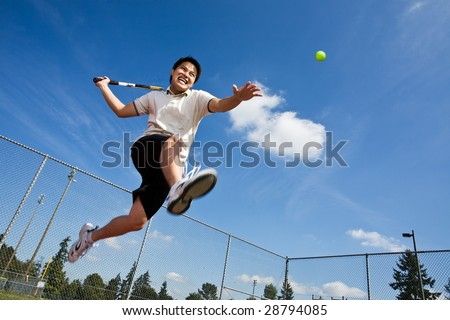 An asian tennis player jumping in the air hitting a tennis ball
